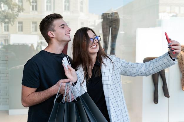 Porträt des glücklichen jungen paares im einkaufszentrum auf schaufensterhintergrund. selfie mit kreditkarten und einkaufstüten.