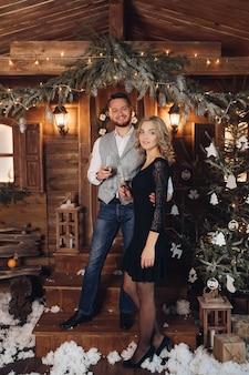 Porträt des glücklichen jungen paares in den eleganten outfits, die von angesicht zu angesicht mit zwei gläsern champagner lächeln
