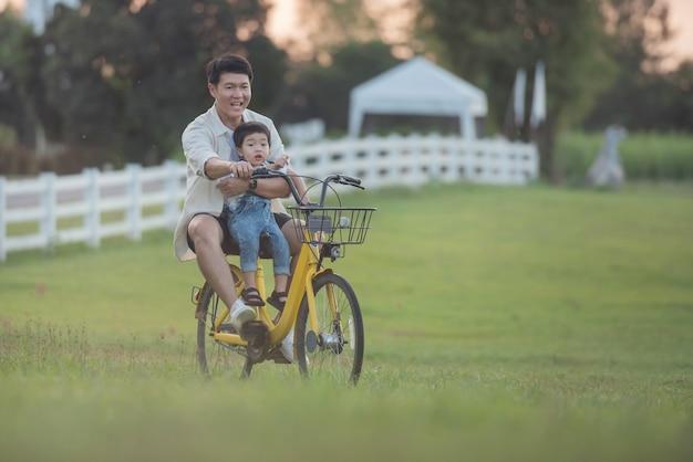 Porträt des glücklichen jungen vaters und des sohns auf einem fahrrad. vater und sohn spielen bei sonnenuntergang im park. leute, die spaß auf dem feld haben. konzept der freundlichen familie und des sommerurlaubs.