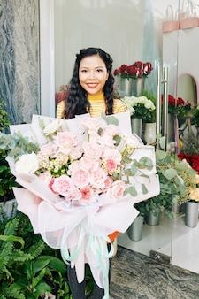 Porträt des glücklichen jungen vietnamesischen floristen, der großen schönen blumenstrauß zeigt, den sie für kunden machte