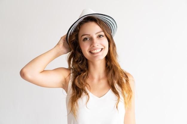 Porträt des glücklichen jungen weiblichen modells, das im sunhat, kamera und das lächeln betrachtend aufwirft.