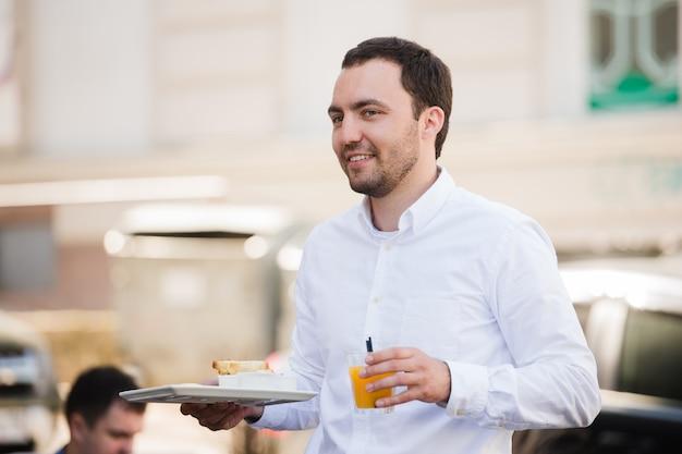 Porträt des glücklichen kellners, der frühstücksmahlzeit und orangensaft am straßencafé hält