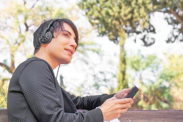 Porträt des glücklichen kerls, der ein smartphone benutzt, um musik mit kopfhörern zu hören.
