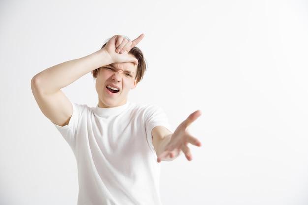 Porträt des glücklichen kerls, der verliererzeichen über stirn zeigt und wegen des sieges und des lachens lächelnd lächelt