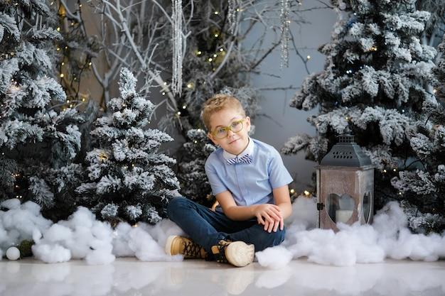 Porträt des glücklichen kinderjungen mit der großen brille, die auf dem boden innenstudio stationiert