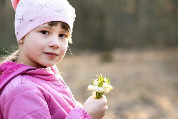 Porträt des glücklichen kindermädchens, das bündel der frühen frühlingsschneeglöckchenblumen draußen hält.