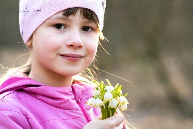 Porträt des glücklichen kindermädchens, das bündel der frühen frühlingsschneeglöckchenblumen im freien hält