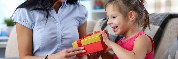 Porträt des glücklichen kindes, das geschenk von der fürsorglichen mutter für urlaub nimmt. lächelnde mama und fröhliche tochter genießen zeit zusammen.