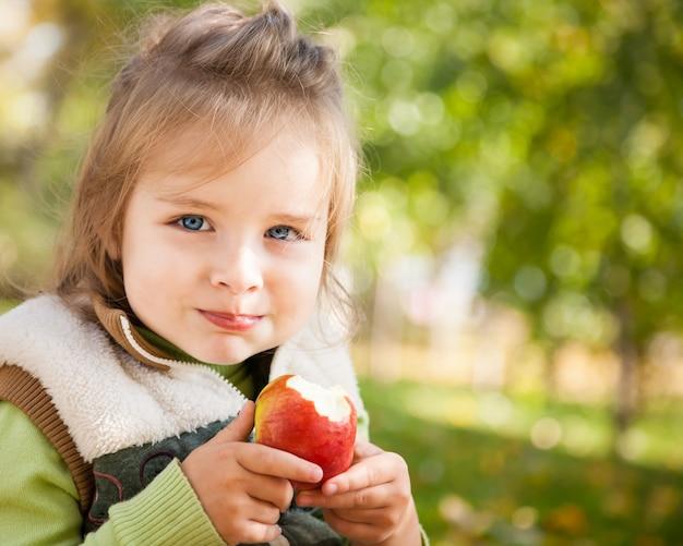 Porträt des glücklichen kindes, das im herbst draußen roten apfel isst