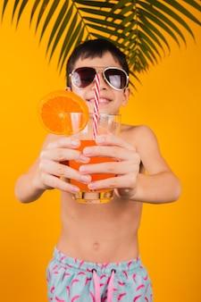Porträt des glücklichen kindes, das orangensaft trinkt - lokalisiert auf gelbem hintergrund.