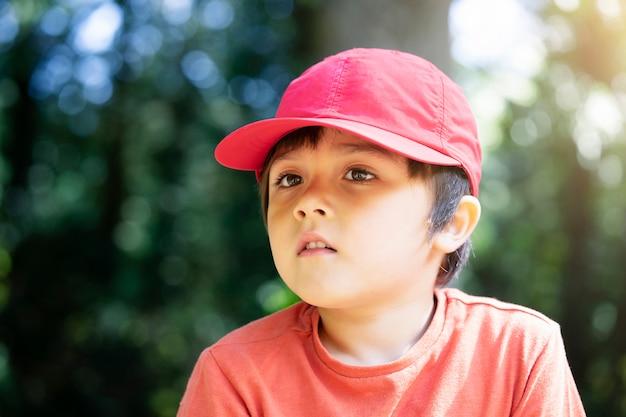 Porträt des glücklichen kindes die rote kappe tragend, die im park mit hellem hellem sonnigem tag sitzt.
