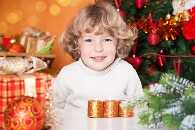 Porträt des glücklichen kindes gegen weihnachtsbaum mit dekorationen