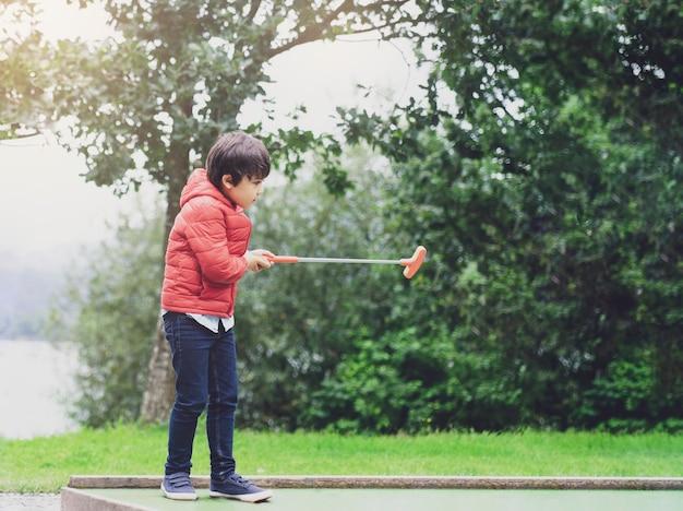 Porträt des glücklichen kindes minigolf im park, aktiver kinderjunge spielend golf am feiertag, kinder, die draußen seine ferientätigkeit genießen