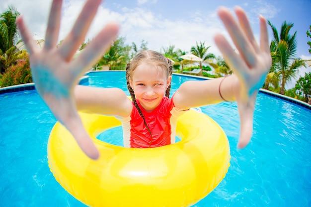 Porträt des glücklichen kindes mit dem aufblasbaren gummikreis, der spaß im swimmingpool hat