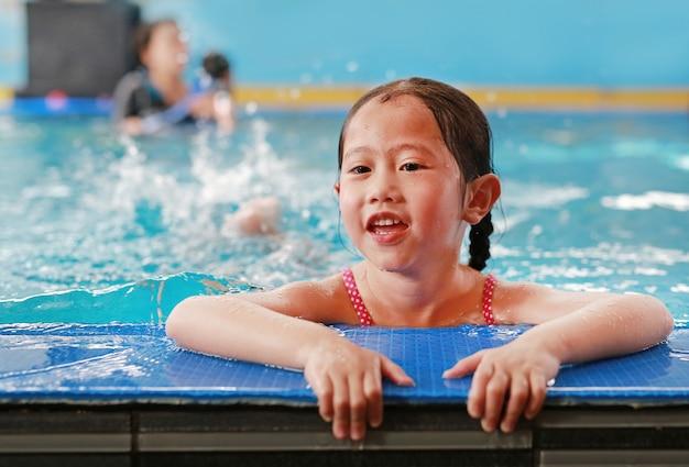 Porträt des glücklichen kleinen asiatischen kindermädchens, das lernt, im pool zu schwimmen. nahaufnahme kurz.