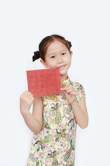 Porträt des glücklichen kleinen asiatischen mädchens, das cheongsam lächelt und roten umschlag hält. frohes chinesisches neujahr.