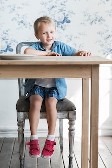 Porträt des glücklichen kleinen jungen, der auf einem alten stuhl vor hölzernem speisetische sitzt