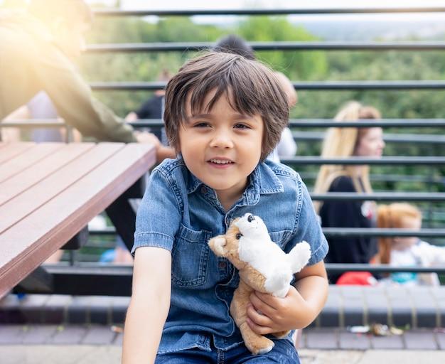 Porträt des glücklichen kleinen jungen, der das hundespielzeug stationiert auf holzbank umarmt und lustiges gesicht macht