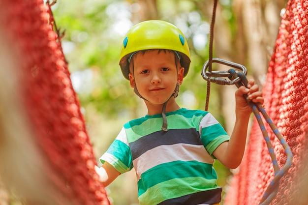 Porträt des glücklichen kleinen jungen, der spaß im erlebnispark lächelt zum tragenden sturzhelm der kamera hat