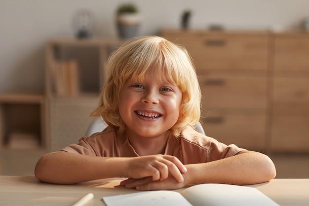 Porträt des glücklichen kleinen jungen mit dem blonden haar lächelnd, während am tisch mit heften sitzen