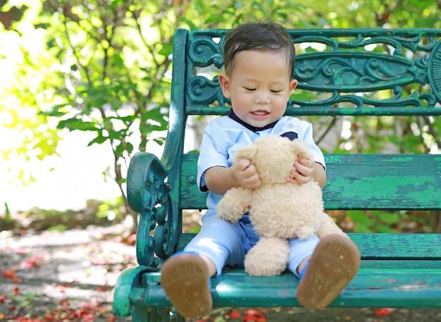 Porträt des glücklichen kleinen jungen mit teddybären im garten.