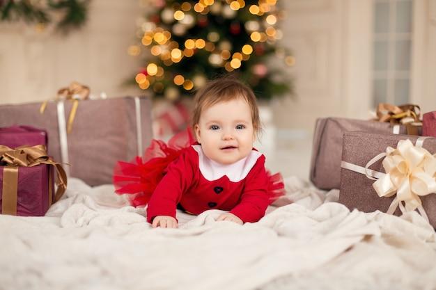 Porträt des glücklichen kleinen mädchens im roten strickpullover mit weihnachtsgeschenkbox nahe weihnachtsbaum.
