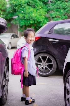 Porträt des glücklichen kleinen mädchens in der thailändischen schuluniform mit dem rucksack, der im parkplatz steht