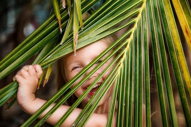 Porträt des glücklichen kleinen mädchens mit palmblatt.