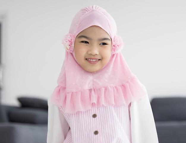 Porträt des glücklichen kleinen muslimischen mädchenkindes mit hijab-kleid smi