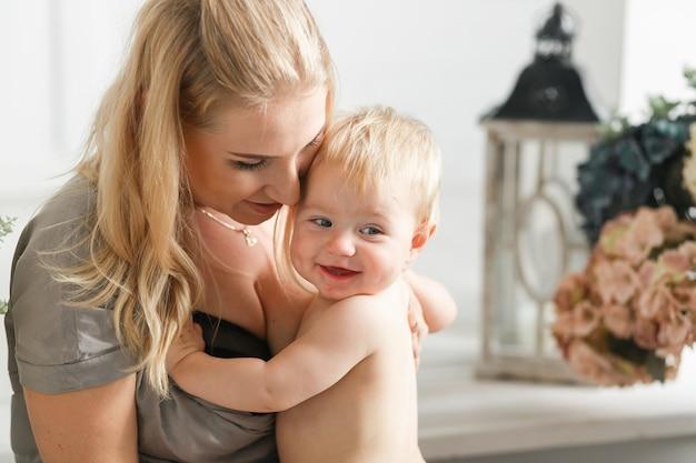 Porträt des glücklichen lachenden babys, das mit fröhlicher junger lächelnder mutter umarmt.