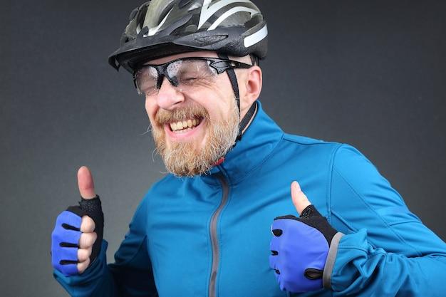 Porträt des glücklichen lachenden bärtigen radfahrers
