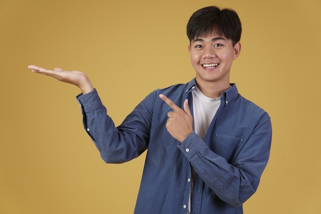 Porträt des glücklichen lächelnden jungen asiatischen mannes gekleidet, der beiläufig zeigenden finger zur leeren offenen hand lokalisiert auf gelb gekleidet