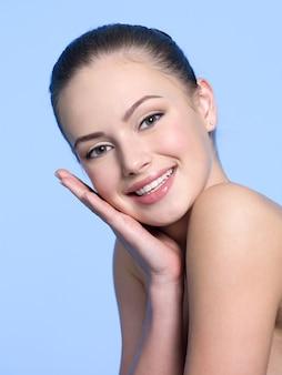 Porträt des glücklichen lächelnden jungen schönen jugendlich mädchens mit frischer haut - blauer raum