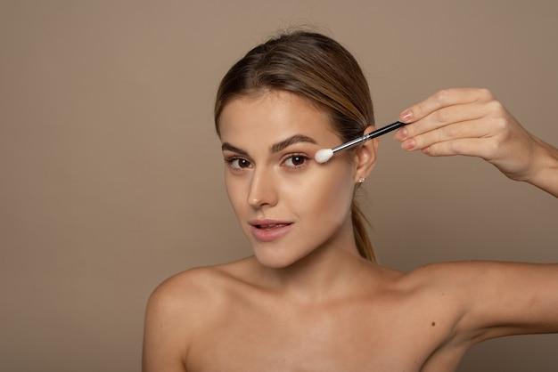 Porträt des glücklichen lächelnden kaukasischen jungen weiblichen modells mit dem schönen gesicht, das gesichtsschminke im studio anwendet. make-up und kosmetikkonzept.