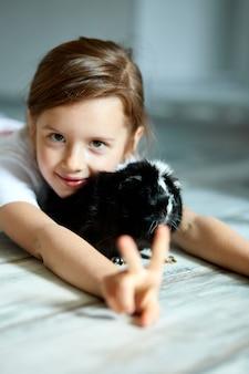 Porträt des glücklichen lächelnden kleinen mädchens, das schwarzes meerschweinchen umarmt.