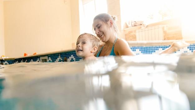 Porträt des glücklichen lächelnden kleinkindjungen, der schwimmen mit mutter im pool lernt. familie hat spaß und entspannung im schwimmbad