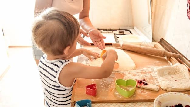 Porträt des glücklichen lächelnden kleinkindjungen mit der jungen mutter, die auf küche backt und kocht. eltern unterrichten und erziehen das kind zu hause