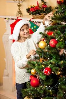 Porträt des glücklichen lächelnden mädchens, das weihnachtsbaum verziert