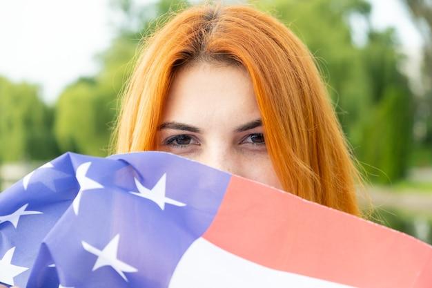 Porträt des glücklichen lächelnden rothaarigen mädchens, das ihr gesicht hinter usa-nationalflagge versteckt