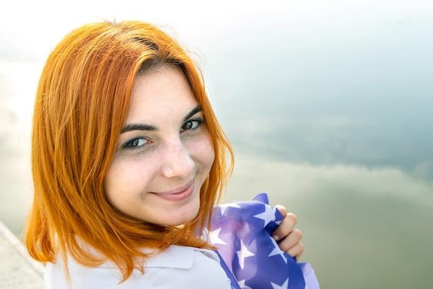Porträt des glücklichen lächelnden rothaarigen mädchens. positive junge frau, die in der kamera draußen schaut.