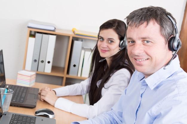 Porträt des glücklichen lächelnden teamkundenbetreuungstelefonbetreibers am arbeitsplatz.