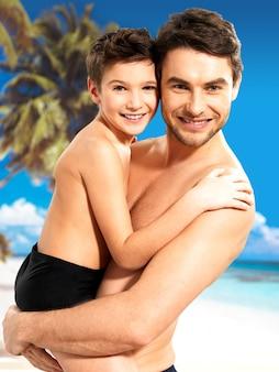 Porträt des glücklichen lächelnden vaters umarmt sohn 8 jahre alt am tropischen strand