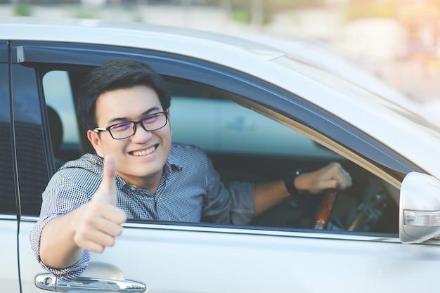 Porträt des glücklichen lächelns junge asiatische mannreisender auf der straße, die daumen nach oben zeigt, während er in seinem auto fährt.