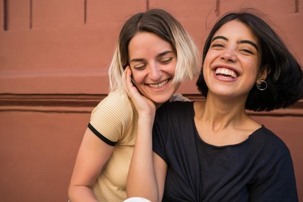 Porträt des glücklichen lesbischen paares, das zeit zusammen verbringt und auf der straße umarmt. lgbt-konzept.