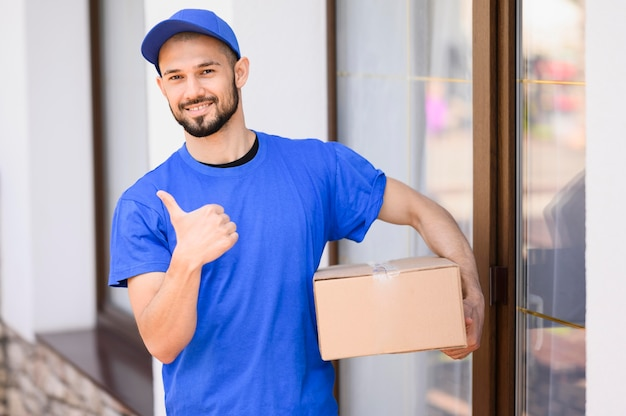 Porträt des glücklichen liefermanns, der box hält