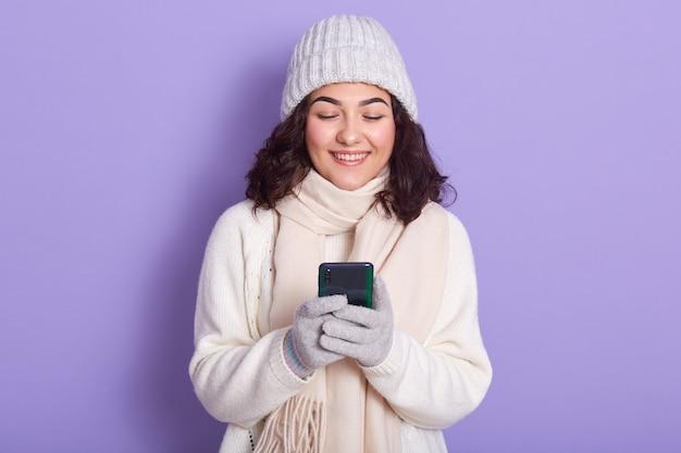 Porträt des glücklichen lockigen haarigen mädchens, das lokalisiert über lila hintergrund im studio aufwirft, smartphone in händen hält