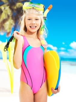 Porträt des glücklichen mädchens, das am strand genießt. schulkind mädchen steht in der hellen farbe badebekleidung mit schwimmmaske auf dem kopf.