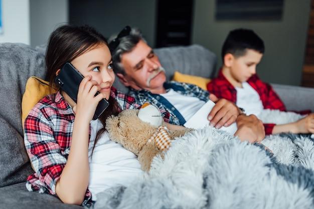 Porträt des glücklichen mädchens, das intelligentes telefon spricht, während es mit ihrem teddybären auf dem bett liegt.