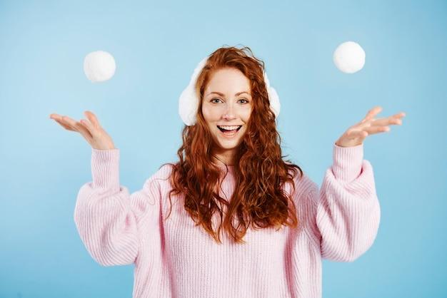Porträt des glücklichen mädchens, das schneeball wirft
