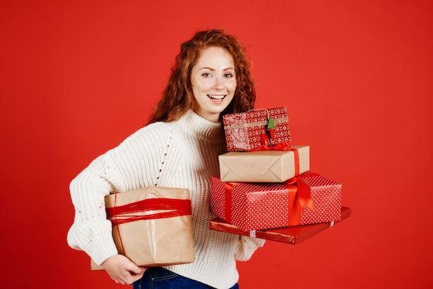 Porträt des glücklichen mädchens, das stapel des weihnachtsgeschenks hält